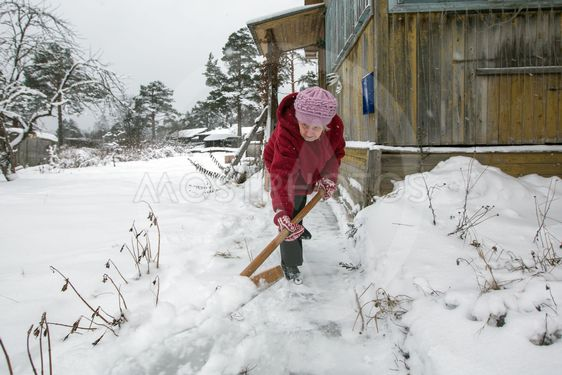 Elderly woman cleans the snow shovel near his home in the...