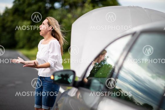 Pretty middle aged woman having car troubles - broken...
