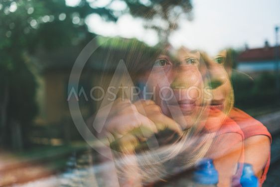 Reflection in the window of a young woman traveling by...
