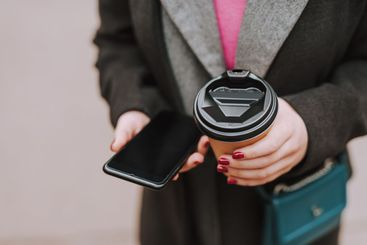 Modern gadget and coffee to go in hands of woman