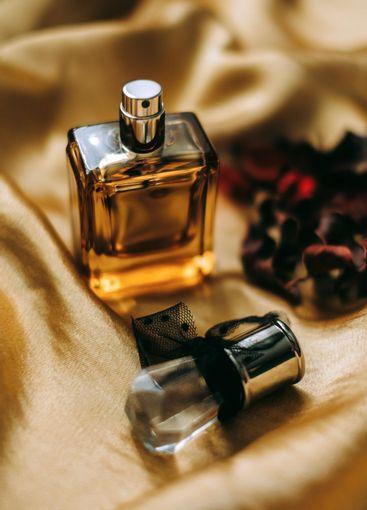 Perfume bottle on golden satin fabric, close-up, warm...