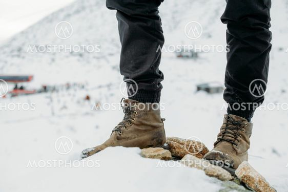 Feet in boots on a background of snowy mountains after a...