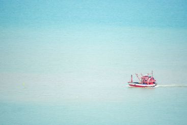 Fishing boats sailing in the sea without waves.