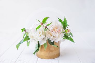Fresh bouquet of white peonies in vintage bowl on light...