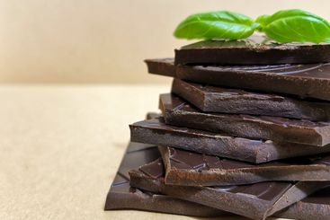 Closeup pieces of dark, inferior chocolate and basil leaves