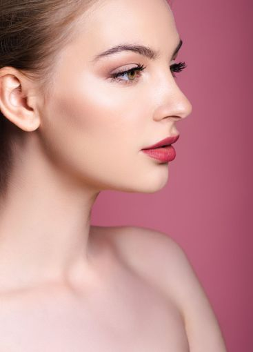 nude and young woman with makeup looking away on pink