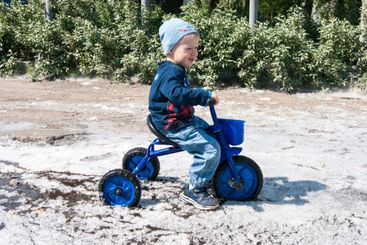 A blond-haired boy in blue rides a small tricycle in a...