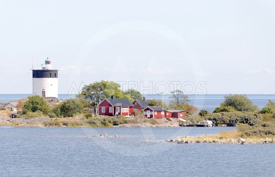 Lighthouse and some small red cottages on a tiny island...