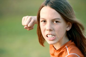 Boy with Long Hair Throws a Punch