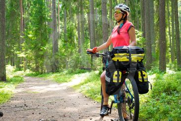Woman riding a bike on the forest trail in sunny day