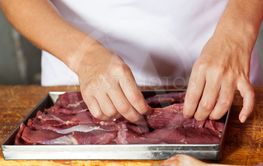 Female Butcher Arranging Meat Slices In Tray