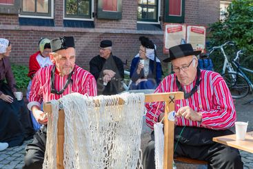 Dutch fair with men in traditional clothing repairing...