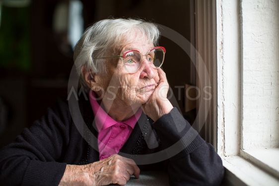 Elderly woman in glasses thoughtfully looking out the...