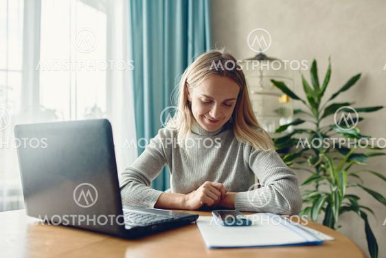 Adoult woman 35s working on laptop and talking online...