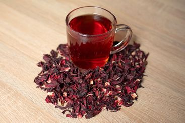 A cup of red tea with hibiscus flowers on a wooden table