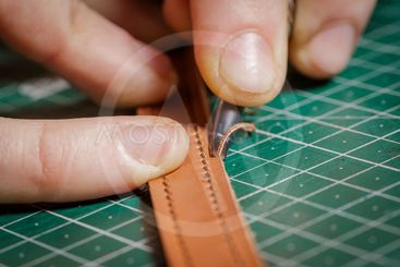 A person working as an artisan in his leather workshop...