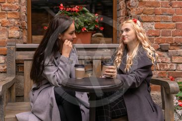 two girls are drinking coffee on the street and talking