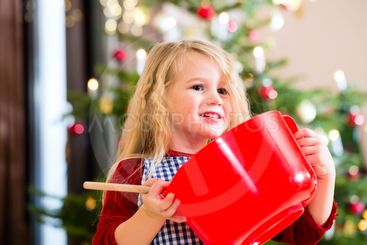 Girl baking cookies in front of Christmas tree