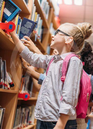 schoolgirls choosing books in library
