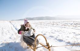 Cute little girl outside in winter nature, sitting on...
