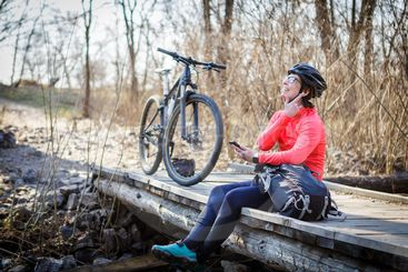 female cyclist listens to music while relaxing on the...