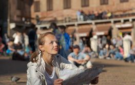 Gorgeous female tourist with a map discovering a foreign...