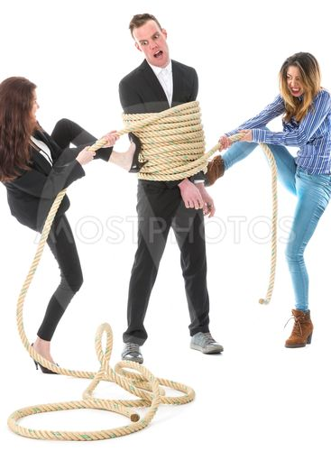 Two angry woman tying a business man with rope