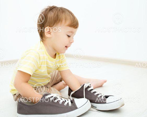 Pojke leker med stora gymnastikskor