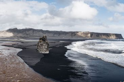 Stormy, moody day on black sand beach Vik Reynisfjara on...