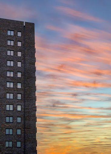 Höghus med många fönster mot orange solnedgång.