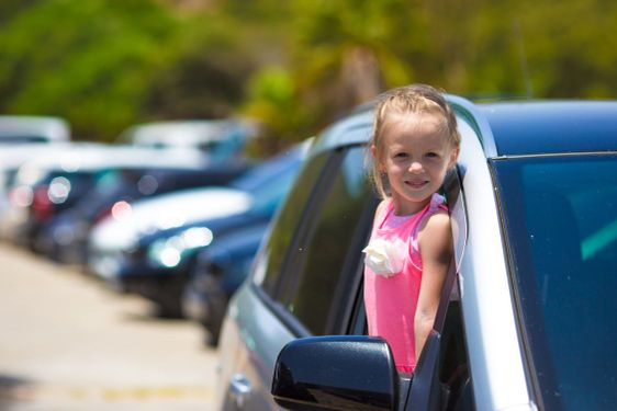 Little adorable girl in the car looking throw window at...