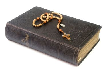 Ancient bible with rosary