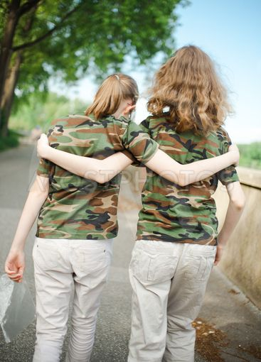 Two teenaged friends in camouflage t shirts.