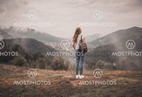 woman standing alone with backpack near mountains