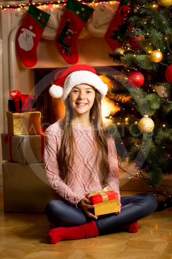 girl in Santa cap on floor with Christmas present at...