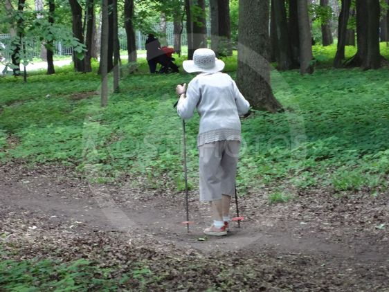 The old lady is engaged in Nordic walking