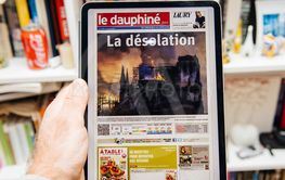 Man reading on iPad Pro about Notre-Dame de Paris fire