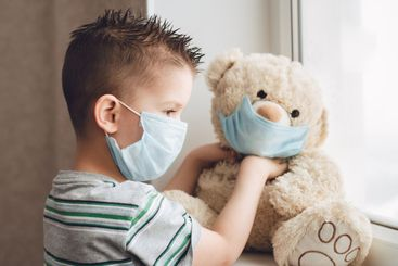 a small child in a mask sits at home in quarantine and...