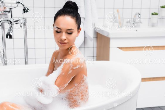Brunette woman looking at wet shoulder while taking bath...