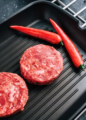 Fresh raw minced beef steak for burgers on black grill...