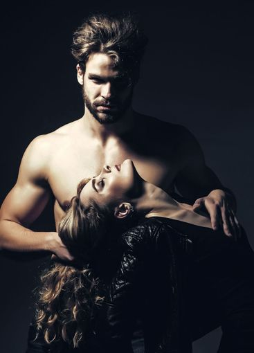 Man with muscular torso hold woman on long hair