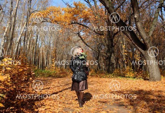 girl walking in autumn park alley
