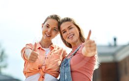 teenage girls or best friend showing thumbs up
