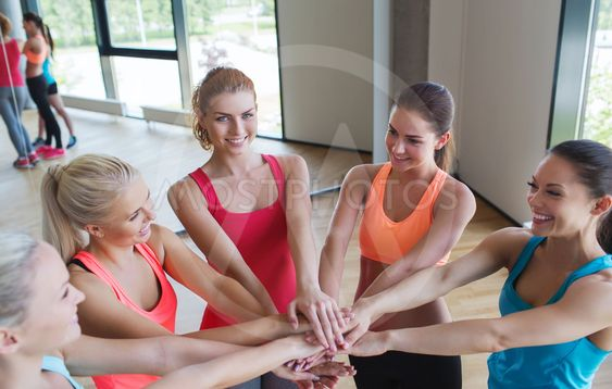 group of women with hands on top in gym