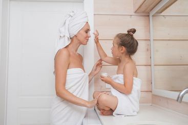 Happy loving family take care of the skin and apply...