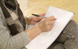 Närbild på kvinnlig elev som skriver med penna i skrivblock