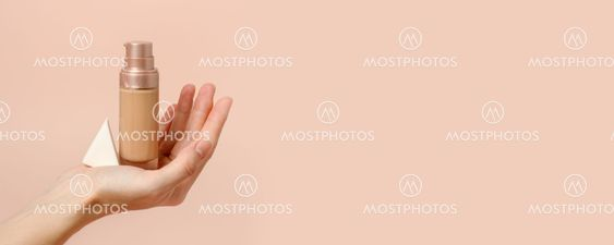 Applying foundation on makeup sponge. Woman's hands with...