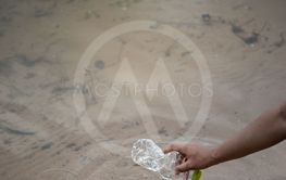 hand pick up plastic bottle from water