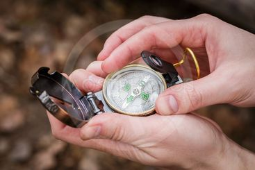 man sets up a compass holding it in his hands