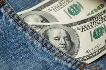 Hundred dollar bank note in the jeans pocket